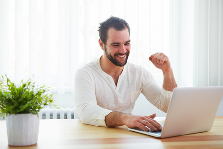 rejoices: Happy man working with laptop in office Stock Photo