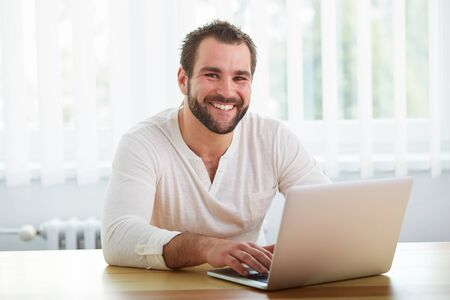 office man: Happy man working with laptop in the office