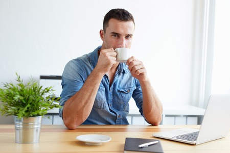gente exitosa: Handsome man drinking coffee in the office during work break