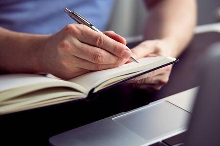 hombre escribiendo: Close up of man writing on paper notebook with pen Foto de archivo