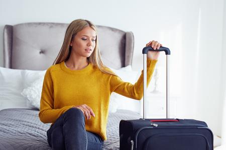 mujeres sentadas: Mujer con maleta sentada en la cama en el hotel