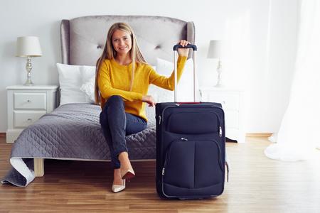 mujeres sentadas: Mujer feliz con la maleta sentada en la cama en el hotel Foto de archivo