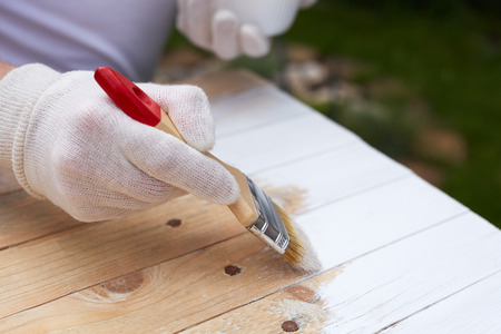 Close up paintbrush in male hand and painting on the wooden board Stock Photo - 80182833