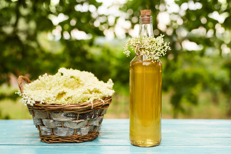 Homemade elderflower syrup in a bottle and basket with flowers of elderflowers