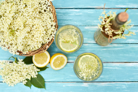 Two glasses of elderflower lemonade and bottle of homemade syrup, top view
