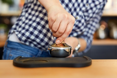 Female barista tamping freshly ground coffee Stock Photo