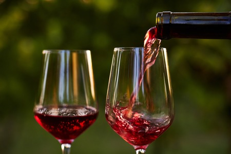 Pouring red wine into glasses in the vineyard Stock Photo