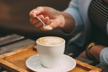 Close-up of a spoon in a female hand pouring sugar into her coffee cup