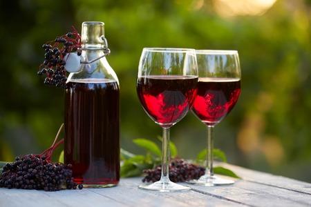 Glasses of elderberry wine and elderberries on wooden table Stok Fotoğraf