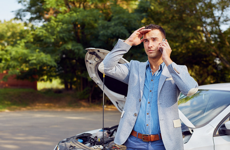Portrait of a man standing at a broken car and calling