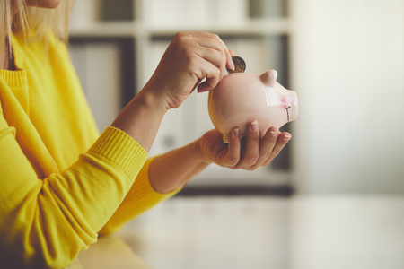 Woman inserts a coin into a piggy bank, toned image Фото со стока