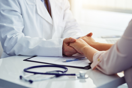 Friendly male doctor reassuring the patient and holding his hands in the office.