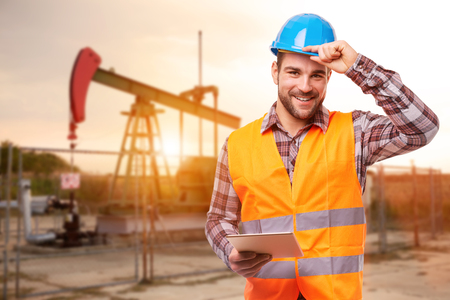 Refinery worker with tablet standing in front of the oil pump