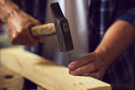 Close up carpenter hammering a nail into wooden plank in his workshop
