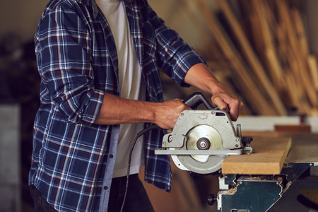 The carpenter using circular saw for cutting wooden board in his workshop