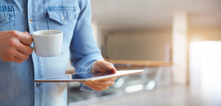 Close up of a male hands holding white digital tablet and cup of coffee