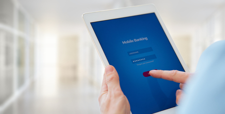 Close up of a male hands holds a tablet with online banking, login page on the touch screen Imagens