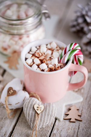 Pink mug of hot chocolate with marshmallows on table, top view