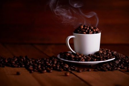 A white cup full of hot coffee beans on a wooden table Imagens
