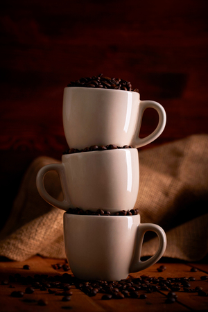 Three cups full of coffee beans on a wooden table Imagens