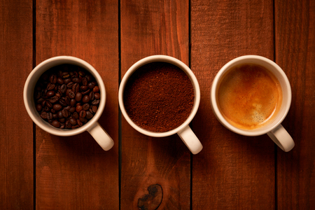 Three cups of espresso, freshly ground coffee and coffee beans on a wooden table from the top view Imagens