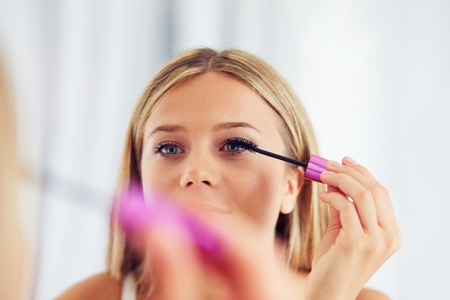 Woman applying makeup and looking in the mirror. Painting eyelashes with mascara