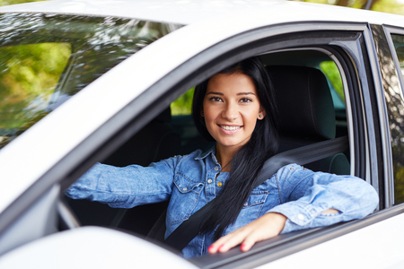 Smiling beautiful woman driving her car