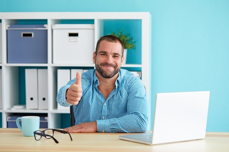 Smiling business man working in modern office and gesturing thumb up