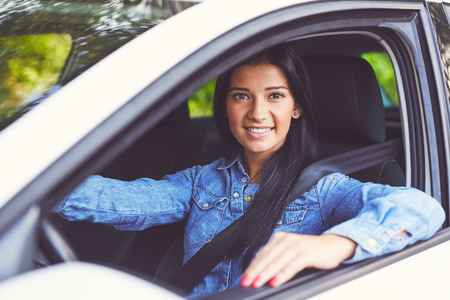 Smiling beautiful woman driving her car. Toned image Imagens
