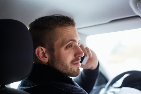 Man sitting in his car and calls with mobile