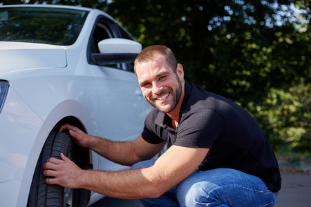 Smiling man examining tires at his new car