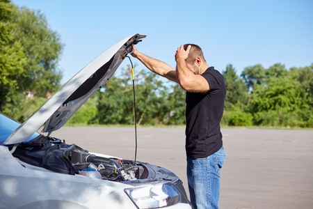 Young man standing in front of a broken car Imagens