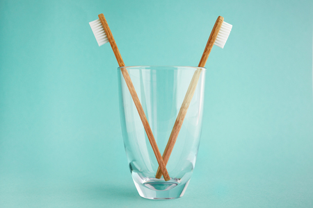 Two bamboo toothbrushes in a glass on a teal background Imagens