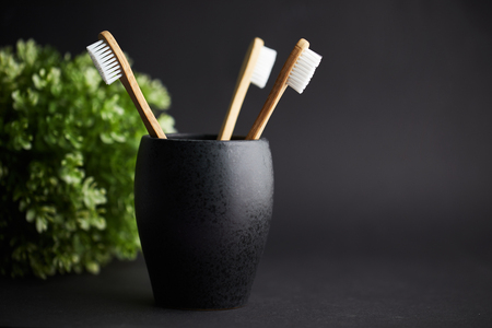 Three bamboo toothbrushes in a black glass with copy space on a dark background
