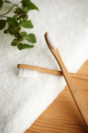 Close up of two bamboo toothbrushes on white towel Imagens