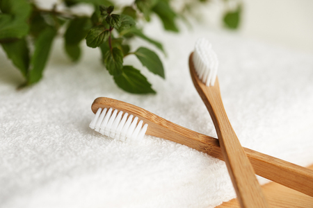 Close up of two bamboo toothbrushes on white towel with plant on background