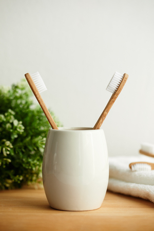 The bamboo toothbrushes in a gray glass in bathroom