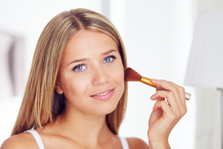 Beautiful woman applying makeup with a big brush and  looking in the camera