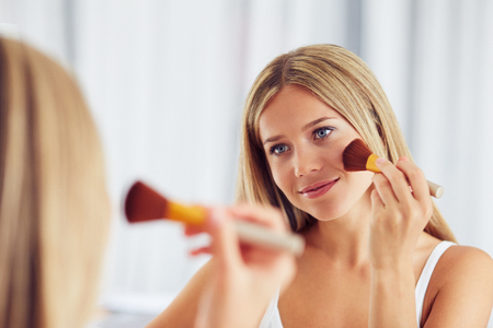 Young woman applying make up with a big brush and looking in the mirror. Focus on her reflection