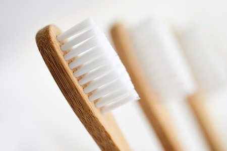 Close up of three bamboo toothbrushes on white background