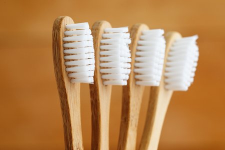 Close up of bamboo toothbrushes on brown background Imagens