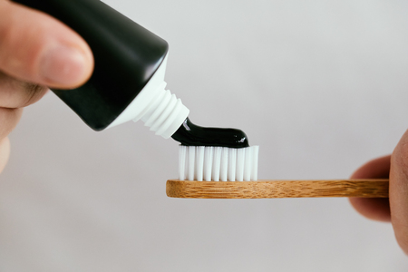 Close up of a male hands with a black toothpaste and a bamboo toothbrush
