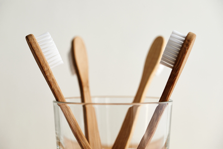 Close up of four bamboo toothbrushes in a glass Imagens