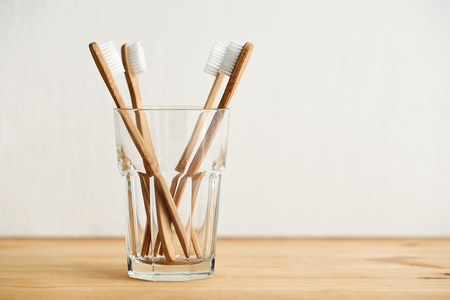 Four bamboo toothbrushes in a glass on a wooden table with copy space Imagens