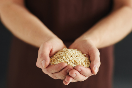 Male hands with a handful of oat flakes