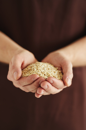 A man with a handful of oat flakes in his hands Imagens