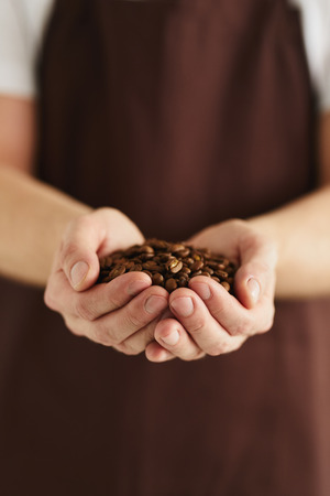 A man with a handful of coffee beans in his hands