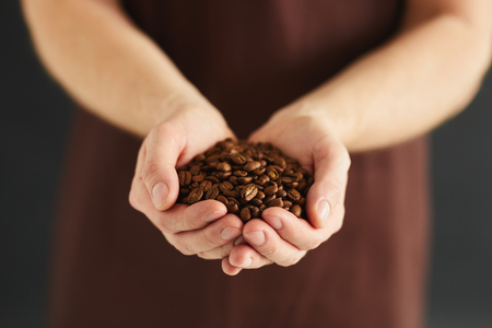 Male hands with a handful of coffee beans