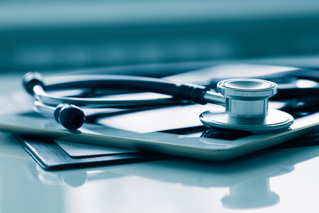 Close up of white tablet and stethoscope on table. Medical equipment on table.