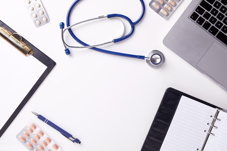 Medical desk with stethoscope, latptop, pills and blank paper on clipboard. Top view of copy space, flat lay shot.